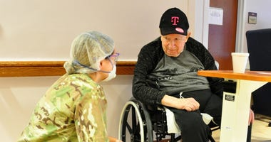 U.S. Army Spc. Olivia Cordero, a Combat Medic with the 1st Battalion, 114th Infantry Regiment, New Jersey Army National Guard (NJARNG), checks on a resident of the New Jersey Veterans Memorial Home at Menlo Park in Edison, N.J., April 17, 2020.