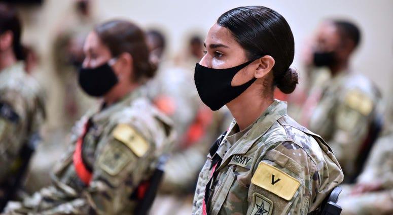 Advanced individual training soldiers wearing face masks listen to Maj. Gen. Dennis LeMaster