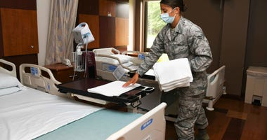 Air Force Airman 1st Class Maria Bandstra, a medical technician assigned to the 316th Aerospace Medicine Squadron, places a towel in a patient room at the Aeromedical Staging Facility at Joint Base Andrews, Md.