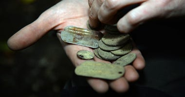 A volunteer displays a pair of dog tags and some coins found at an archeological dig site