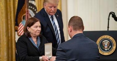 """President Donald J. Trump looks on as Susan Rescorla shows the Presidential Citizens Medal, posthumously awarded to her husband Richard """"Rick"""" C. Rescorla, to her son Trevor Thursday, Nov. 7, 2019."""