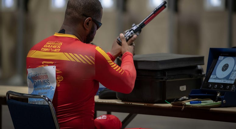 U.S. Marine Corps Veteran Staff Sgt. Anthony Reingoud, Team Marine Corps, reloads his weapon during the 2019 DoD Warrior Games shooting competition finals