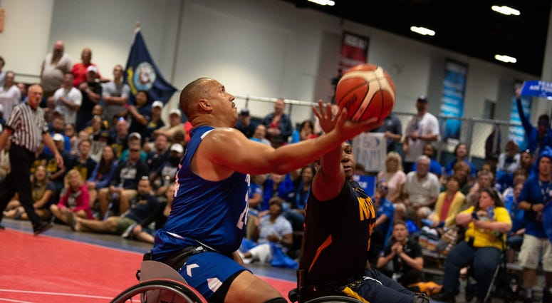 U.S. Air Force Senior Master Sgt. Brian Williams, Team Air Force, puts up a contested layup during the 2019 DoD Warrior Games wheelchair basketball gold medal game