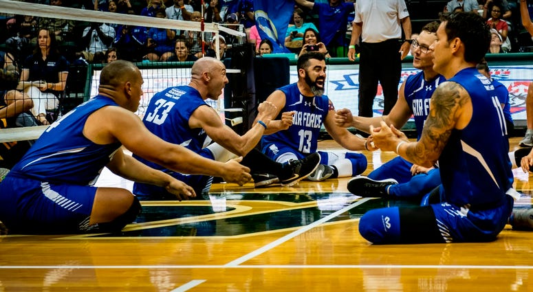 Team Air Force athletes celebrate after forcing a third game during the Department of Defense Warrior Games sitting volleyball finals