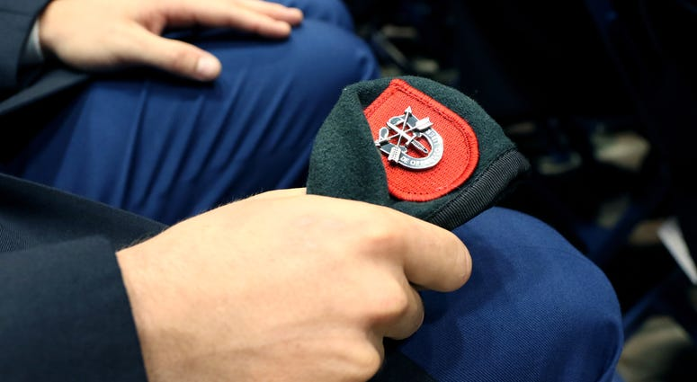 A Soldier from the U.S. Army John F. Kennedy Special Warfare Center and School, clutches his newly awarded green beret during a Regimental First Formation at the Crown Arena in Fayetteville, North Carolina August 1, 2019. The ceremony marked the completio