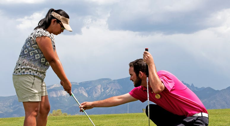 Twin Warriors Golf Club pro Allan McDermott provides swing technique advice to U.S. Marine Corps Veteran Phoebe Comeau during a golf outing at the Twin Warriors Golf Club, Bernalillo, New Mexico.
