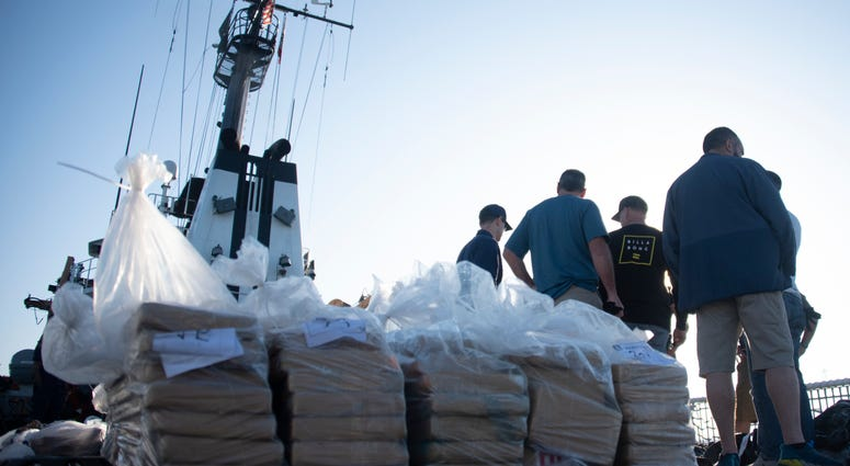Coast Guardsmen prepare bails of cocaine to be offloaded
