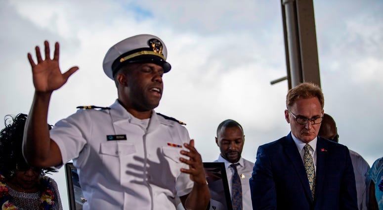 Acting Secretary of the Navy Thomas B. Modly, right, bows his head during an invocation following the unveiling of the new Ford-class aircraft carrier USS Doris Miller (CVN 81)