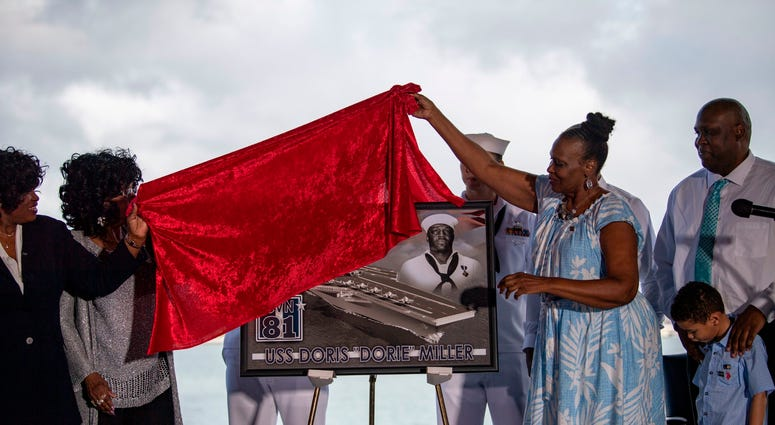 Family of late Ship's Cook 3rd Class Doris Miller unveil a plaque commemorating the future Navy ship, Ford-class aircraft carrier USS Doris Miller (CVN 81)