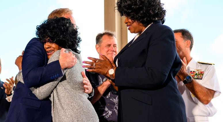 "Brenda Haven, niece of World War II hero Doris ""Dorie"" Miller, hugs Acting Secretary of the Navy Thomas B. Modly after the unveiling of the new Ford-class aircraft carrier USS Doris Miller (CVN 81)"