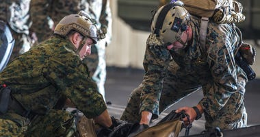 Marines pack equipment in a combat rubber raiding craft in preparation for search and rescue operations
