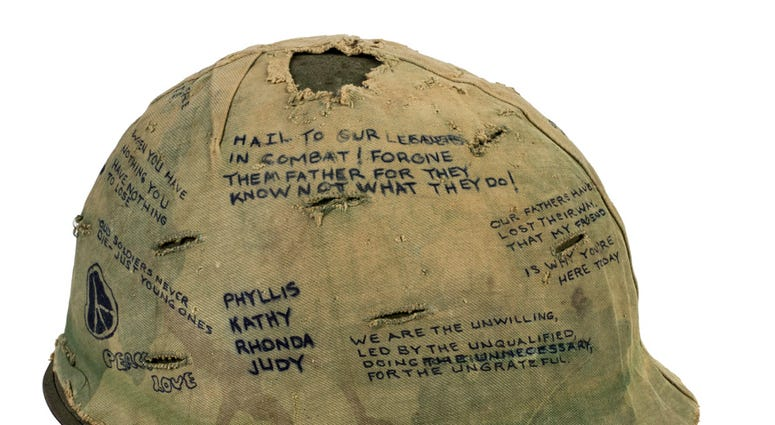 """Veteran Sal Gonzalez wore this helmet liner at the meat-grinder battle dubbed """"Hamburger Hill."""" In May 1969, scores of Americans died or were wounded in repeated assaults up heavily defended Ap Bia Mountain."""