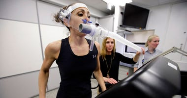 Research scientist Leila Walker, left, is assisted by nutritional physiologist Holly McClung, center, as they demonstrate equipment designed to evaluate fitness levels in female soldiers, who have joined elite fighting units such the Navy Seals.