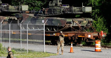 Military police walk near Abrams tanks on a flat car in a rail yard, Monday, July 1, 2019, in Washington, ahead of a Fourth of July celebration that President Donald Trump says will include military hardware.