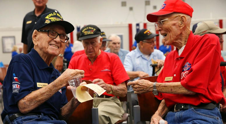 World War II veterans George Thomas, 97, left, and Clark Wilson, 93, enjoy conversation before a ceremony