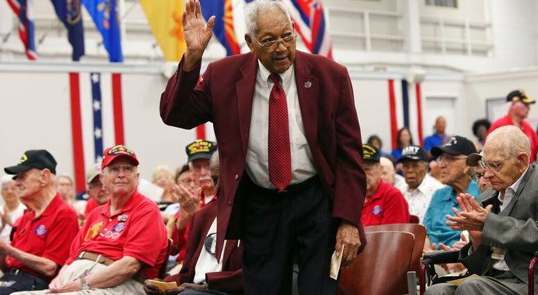 Tuskegee Airmen James L. Bynum, 98, waves as he is introduced during a ceremony at Joint Base San Antonio-Fort Sam Houston