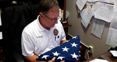 Danny Theriot, the Terrebonne Coroner's Office chief investigator, holds a flag