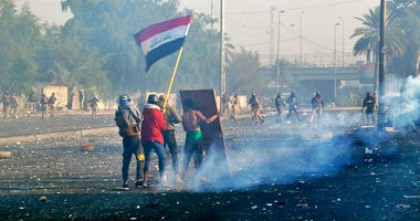 Protesters wave the national flag as security forces fire tear gas during an ongoing protest in central Baghdad, Iraq