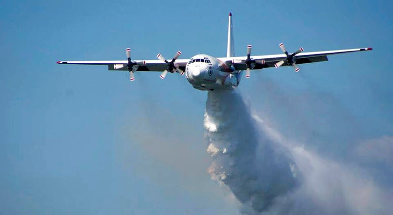 """In this undated photo released from the Rural Fire Service, a C-130 Hercules plane called """"Thor"""" drops water during a flight in Australia."""