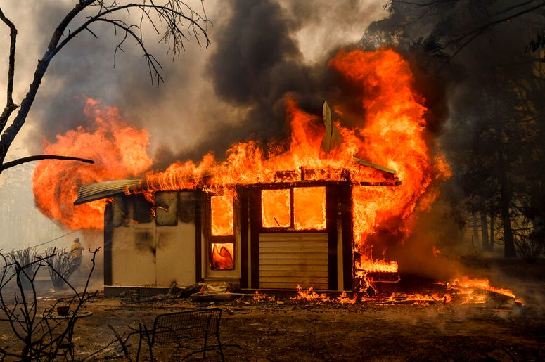 In this Thursday, Jan. 23, 2020, file photo, a firefighter battles the Morton Fire as it consumes a home near Bundanoon, New South Wales, Australia.