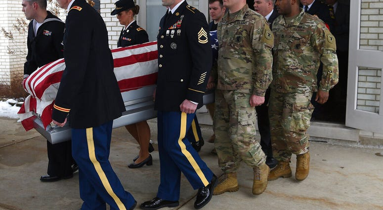 Active duty military members who were in attendance carry the casket.