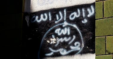 This Oct. 16, 2017, file photo shows the black al-Qaida flag is sprayed on the wall of a damaged school