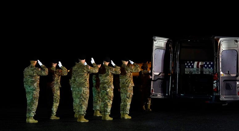 A U.S. Army carry team salutes as door attendant Staff Sgt. Tiliyah Tillman closes the vehicle doors after moving the transfer cases containing the remains of Sgt. 1st Class Javier Gutierrez, of San Antonio, Texas, and Sgt. 1st Class Antonio Rodriguez