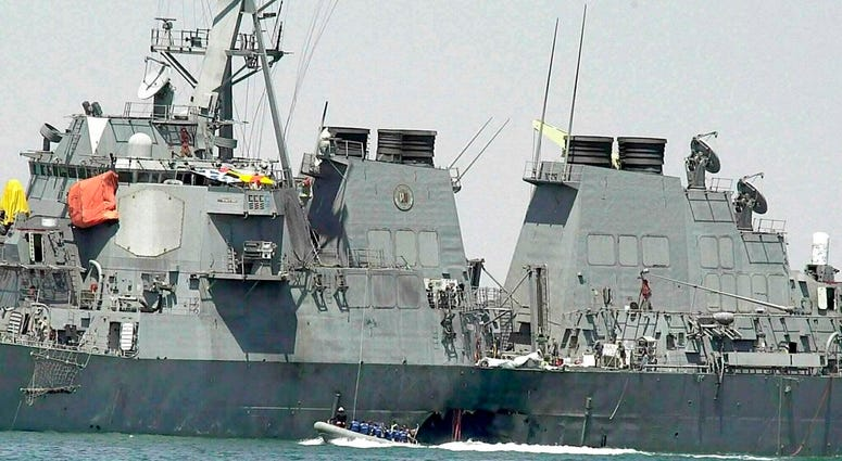 In this Oct. 15, 2000 file photo, experts in a speed boat examine the damaged hull of the USS Cole
