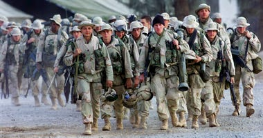 In this Dec. 31, 2001, file photo, U.S. Marines with full battle gear prepare to leave the U.S. military compound at Kandahar