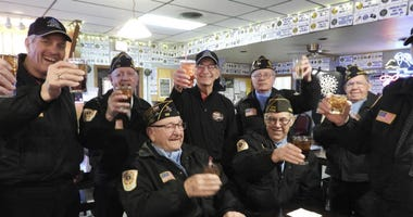 Fellow members of the Sturgis Honor Guard raise a glasses to Arvid Meland, left, who completed his 3,000th honor guard service.