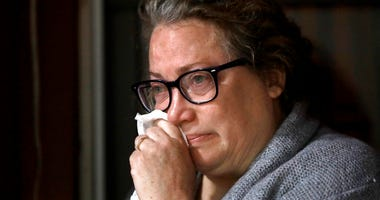 Susan Kenney, of Ware, Mass., who lost her father to the coronavirus, is tearful while speaking to a reporter from The Associated Press