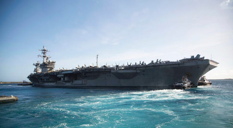 In this photo provided by the U.S. Marine Corps, the aircraft carrier USS Theodore Roosevelt (CVN 71) departs Apra Harbor at Naval Base Guam on Thursday, May 21, 2020
