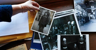 Emily DiPalma Aho looks over photographs and memorabilia of her father, Emilio DiPalma, a World War II veteran