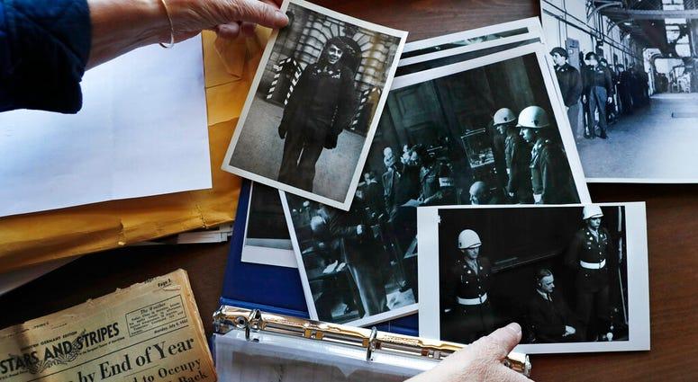 Emily DiPalma Aho looks over photographs and memorabilia of her father, Emilio DiPalma, a World War II veteran