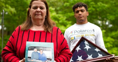 In this Friday, May 22, 2020, photo Florence Hopp, left, holds a photograph of herself and her husband Robert Hopp