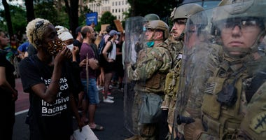 Soldiers with Utah National Guard stand near a group of demonstrators that gathered to protest the death of George Floyd