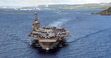 In this June 4, 2020, photo provided by the U.S. Navy, the aircraft carrier USS Theodore Roosevelt (CVN 71) departs Apra Harbor in Guam