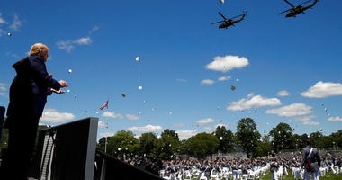 President Donald Trump applauds as Army helicopters fly over and West Point cadets toss their caps into the air at the end of commencement ceremonies on the parade field, at the United States Military Academy