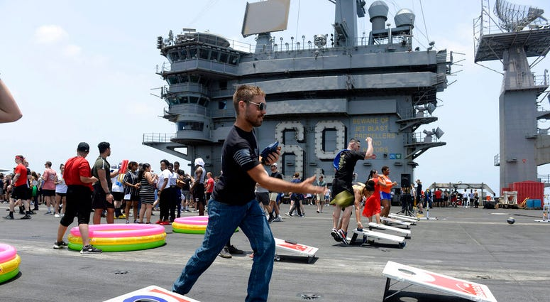 Sailors participate in sporting events on the flight deck of the aircraft carrier USS Dwight D. Eisenhower