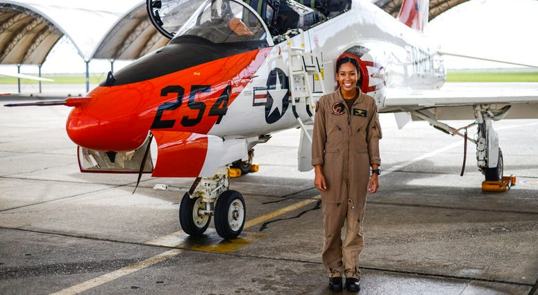 In this photo provided by the U.S. Navy, student Naval aviator Lt. j.g. Madeline Swegle, assigned to the Redhawks of Training Squadron (VT) 21 at Naval Air Station Kingsville, Texas, stands by a T-45C Goshawk training aircraft