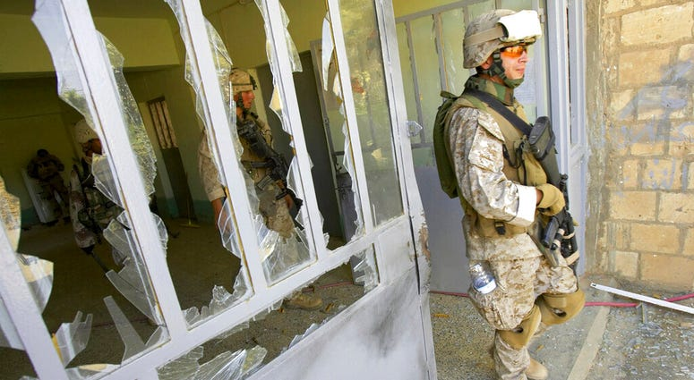 This file photo from Aug. 6, 2005, shows U.S. Marine Staff Sgt. Brian Hamilton of Columbus, Ohio, from Lima Company of the 3rd Battalion, 25th Regiment as he exits after searching a school