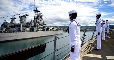 Sailors aboard the guided-missile destroyer USS Michael Murphy (DDG 112) render honors to Battleship Missouri Memorial