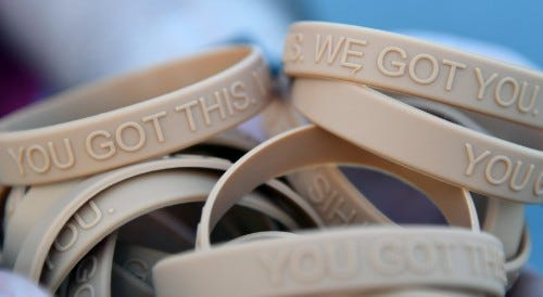 """Bracelets, labeled with the message, """"You Got This. We Got You,"""" are handed out to participants during the Dragon March on Keesler Air Force Base, Mississippi, Sept. 13, 2019. The three-mile walk was held as part of the wing stand down day directed by Air"""