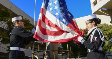 Sailors assigned to Naval Medical Center San Diego (NMCSD), raise the flag during a special morning colors in observance of Veteran's Day.