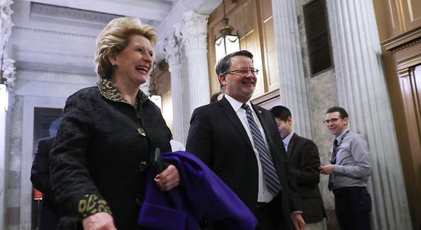 : Sen. Debbie Stabenow (D-MI) and Sen. Gary Peters (D-MI) make their way to the Senate Chamber for early morning votes at the U.S. Capitol February 9, 2018 in Washington, DC. Despite an attempt by Sen. Rand Paul (R-KY) to slow down the process, the Senate