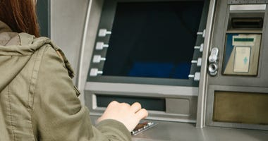 A young woman takes money from an ATM