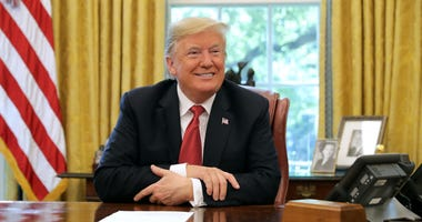 U.S. President Donald Trump talks to reporters while hosting workers and members of his cabinet for a meeting in the Oval Office at the White House October 17, 2018 in Washington, DC.