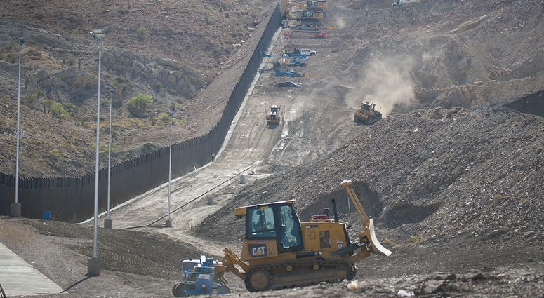 Construction crews work on a border wall being put in place by We Build The Wall Inc. in Sunland Park, New Mexico.
