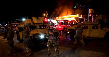 Members of the National Guard hold a perimeter as a fire crew works to put out a fire at a gas station on Lake Street on May 29, 2020 in Minneapolis, Minnesota.