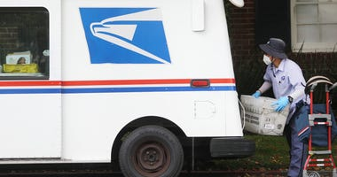 A U.S. Postal Service (USPS) worker wears a mask and gloves amidst the coronavirus pandemic on April 13, 2020 in Santa Monica, California.